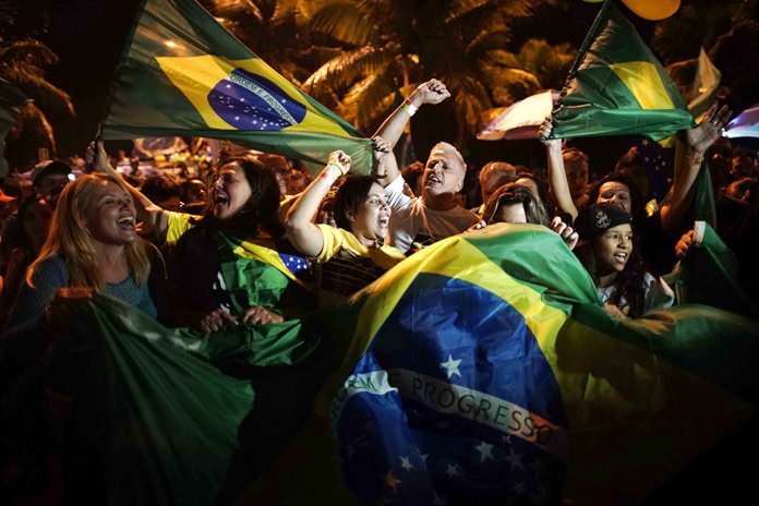 Supporters of Jair Bolsonaro celebrate in front of his residence in Rio de Janeiro, Brazil, Sunday, Oct. 28. (AP Photo/Leo Correa)