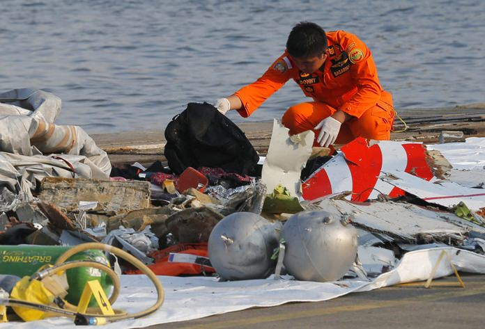 A member of Indonesian Search and Rescue Agency (BASARNAS) inspects debris believed to be from a Lion Air passenger jet that crashed off Java Island at Tanjung Priok Port in Jakarta, Indonesia Monday, Oct. 29. (AP Photo/Tatan Syuflana)