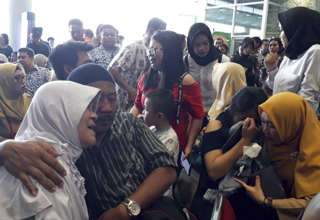 Relatives of passengers comfort each other as they wait for news. (AP Photo)