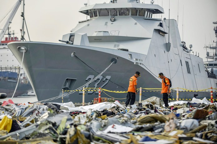 Members of National Search and Rescue Agency inspect debris retrieved from the waters where Lion Air flight JT 610 is believed to have crashed, at Tanjung Priok Port in Jakarta, Indonesia, Wednesday, Oct. 31. (AP Photo/Fauzy Chaniago)