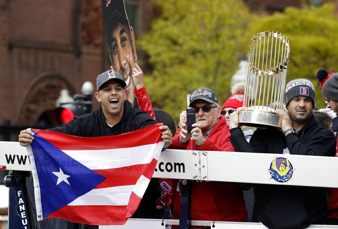 Boston Red Sox manager Alex Cora, left, waves the flag of Puerto Rico as coach Ramon Vazquez holds the championship trophy during a parade to celebrate the team's World Series championship over the Los Angeles Dodgers, Wednesday, Oct. 31, in Boston. (AP Photo/Elise Amendola)