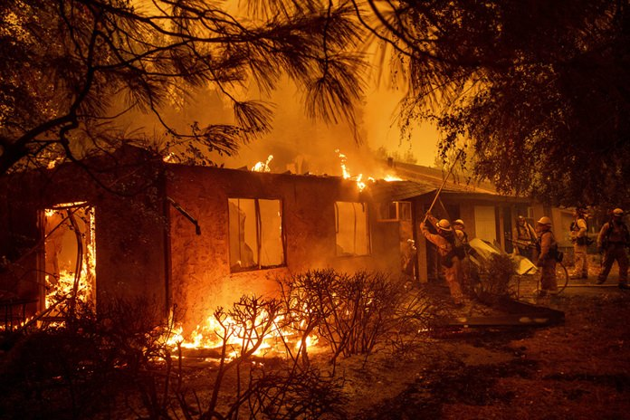 Firefighters work to keep flames from spreading through the Shadowbrook apartment complex as a wildfire burns through Paradise, Calif., on Friday, Nov. 9. (AP Photo/Noah Berger)