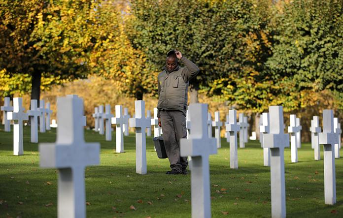 A cemetery employee walks between graves of American serviceman killed during WWI ahead of celebrations of the WWI centenary at the American Cemetery in Suresnes, on the outskirts of Paris. (AP Photo/Vadim Ghirda)