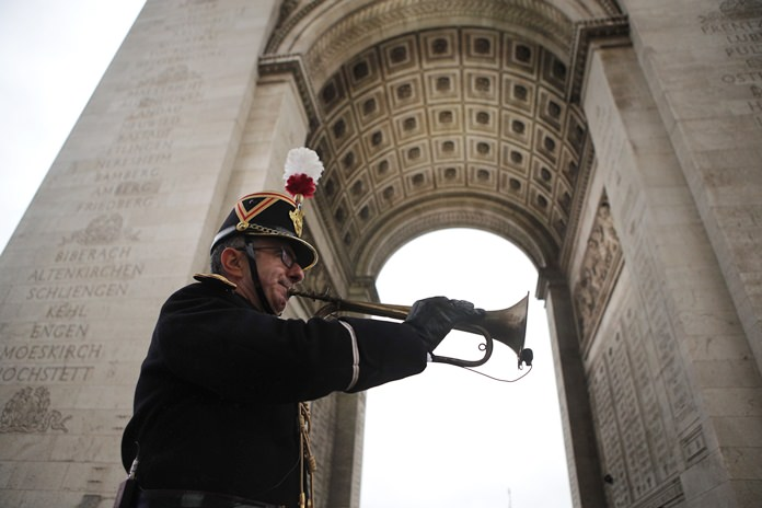 """Military officer Garcia plays the original Armistice bugle from 1918 under the Arc de Triomphe Sunday, Nov. 11, 2018 in Paris. More than 60 heads of state and government attended the Armistice ceremonies at the Tomb of the Unknown Soldier in Paris on the 11th hour of the 11th day of the 11th month, exactly a century after the armistice. World leaders with the power to make war but a duty to preserve peace solemnly marked the end of World War I's slaughter 100 years ago at commemorations Sunday that drove home the message """"never again"""" but also exposed the globe's new political fault lines. (AP Photo/Francois Mori, Pool)"""