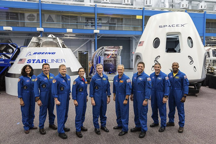 From left, Sunita Williams, Josh Cassada, Eric Boe, Nicole Mann, Christopher Ferguson, Douglas Hurley, Robert Behnken, Michael Hopkins and Victor Glover stand in front of mockups of Boeing's CST-100 Starliner and SpaceX's Crew Dragon capsules at the Johnson Space Center in Texas. This month, NASA said that the first commercial test flights have slipped from late 2018 into 2019. (NASA via AP)
