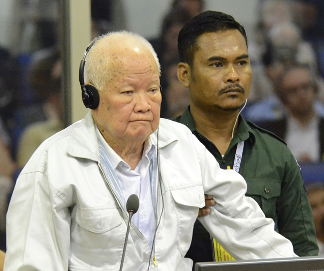 Khieu Samphan, foreground, former Khmer Rouge head of state, stands at a dock in a court room during a hearing at the U.N.-backed war crimes tribunal in Phnom Penh, Cambodia, Friday, Nov. 16. A U.N.-backed tribunal in Cambodia on Friday convicted the two most senior surviving leaders of the country's former Khmer Rouge regime of genocide and other crimes against humanity, sentencing them to life in prison. (Nhet Sok Heng/Extraordinary Chambers in the Courts of Cambodia via AP)