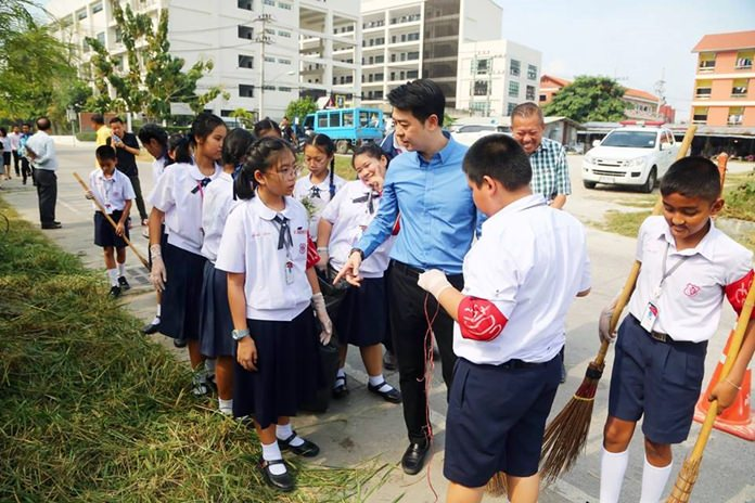 Students from Aksorn Suksa School joined Pattaya sanitation workers in collecting garbage and cleaning the area behind Banglamung Hospital.