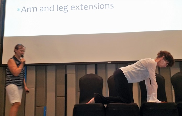 Diana Mountanos from Pure Yoga assists by performing several exercises as Gay Burnett from Surecell Medical describes them and their purpose in helping to alleviate or avoid back pain.