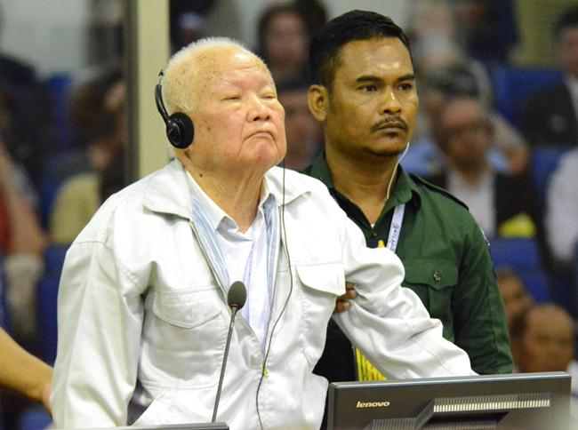Khieu Samphan, left, former Khmer Rouge head of state, stands at the dock in a court room during a hearing at the U.N.-backed war crimes tribunal in Phnom Penh, Cambodia, Friday, Nov. 16. (Nhet Sok Heng/Extraordinary Chambers in the Courts of Cambodia via AP)