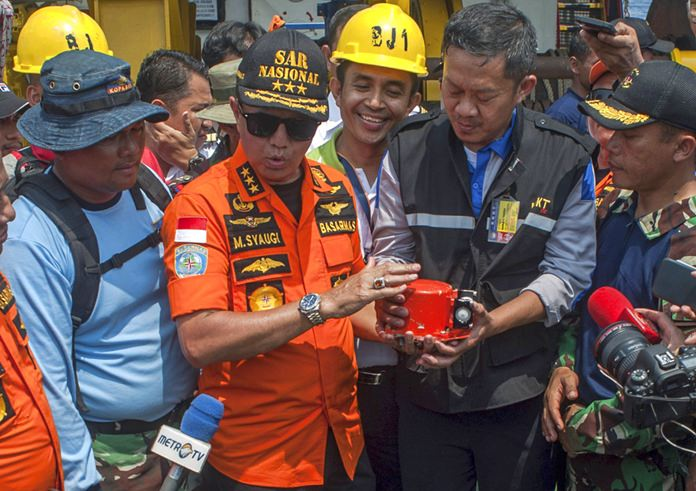 Chief of National Search and Rescue Agency Muhammad Syaugi, center, holds the flight data recorder from the crashed Lion Air jet during a press conference, onboard a rescue ship anchored in the waters of Tanjung Karawang, Indonesia, Thursday, Nov. 1. (AP Photo/Fauzy Chaniago)