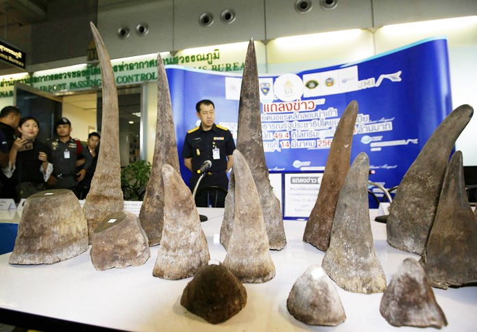 In this March 14, 2017, file photo, Thai Customs officers stand behind seized rhino horns at the customs office at Suvarnabhumi airport. (AP Photo/Sakchai Lalit)