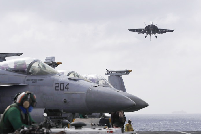An F/A-18 Super Hornet fighter jet lands on the deck of the U.S. Navy USS Ronald Reagan in the South China Sea, Tuesday, Nov. 20. (AP Photo/Kin Cheung)