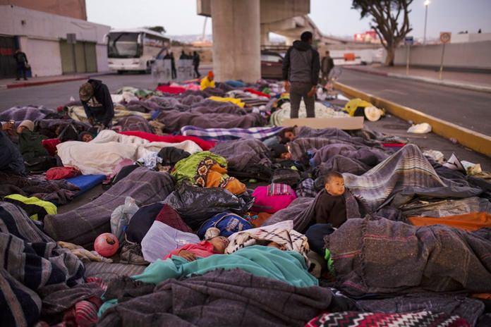 Migrants sleep under a bridge at the Chaparral border crossing in Tijuana, Mexico, Friday, Nov. 23. (AP Photo/Rodrigo Abd)