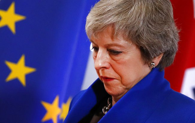 British Prime Minister Theresa May walks past the EU flag at the conclusion of an EU summit in Brussels, Sunday, Nov. 25. (AP Photo/Alastair Grant)