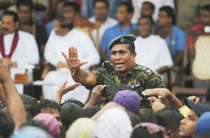 A Sri Lankan police officer tries to control supporters of Sri Lankan president Maithripala Sirisena and his newly appointed prime minister Mahinda Rajapaksa during a rally held outside the parliamentary complex in Colombo, Sri Lanka, Monday, Nov. 5. (AP Photo/Eranga Jayawardena)