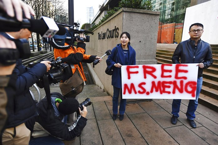 People hold a sign at a Vancouver, British Columbia courthouse prior to the bail hearing for Meng Wanzhou, Huawei's chief financial officer on Monday, December 10. (Jonathan Hayward/The Canadian Press via AP)