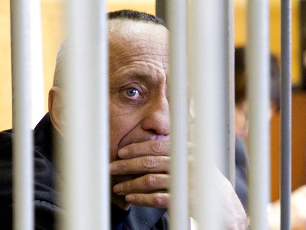 Mikhail Popkov looks through bars during a court session in Irkutsk, Russia, Monday, Dec. 10. (Julia Pykhalova, Komsomolskaya Pravda via AP)