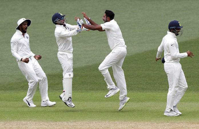India's Ravi Ashwin, second right, celebrates with teammate Rishabh Pant after taking the wicket of Australia's Josh Hazlewood for India to win the first cricket test by 31 runs in Adelaide, Australia, Monday, Dec. 10. (AP Photo/James Elsby)