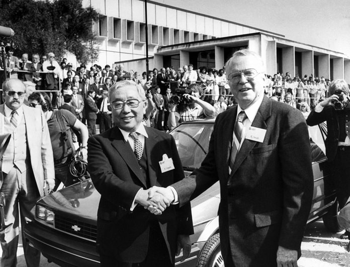 In this April 13, 1985 file photo, then Toyota Motor Corp. Chairman Eiji Toyoda (left) and then General Motors Corp. Chairman Roger B. Smith shake hands in front of a Chevrolet Nova at the new United Motor Manufacturing Inc. plant in Fremont, Calif. (AP photo/Paul Sakuma)
