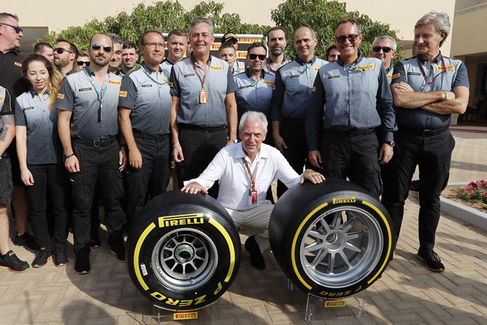 Pirelli CEO Marco Tronchetti Provera (center) poses with his staff behind the new Pirelli tyre ahead of the Emirates Formula One Grand Prix at the Yas Marina racetrack in Abu Dhabi, Sunday, Nov. 25. (AP Photo/Hassan Ammar)