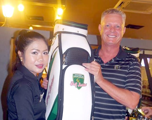Ken Price (right) receives his prize golf bag.