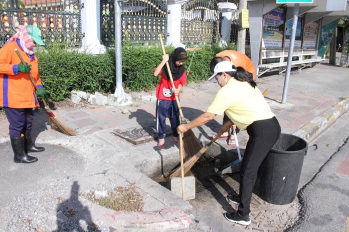 Residents in the Ton Krabok Community take part in a neighborhood cleanup, picking up trash and sweeping streets.