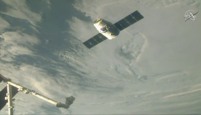 In this image taken from NASA Television, the SpaceX Dragon cargo spacecraft full of Christmas goodies approaches the robotic arm for docking to the International Space Station, Saturday, Dec. 8, 2018. (NASA TV via AP)