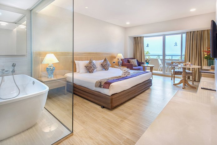 Ocean Deluxe room features white and sandy tan accents, marble bathroom and amenities.