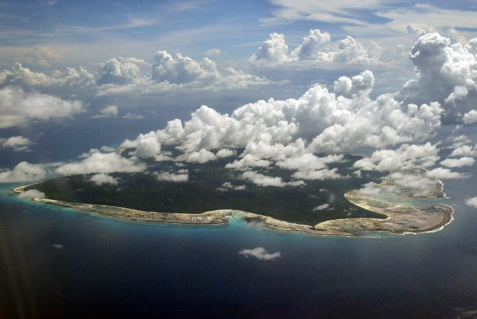 In this Nov. 14, 2005 file photo, clouds hang over the North Sentinel Island, in India's southeastern Andaman and Nicobar Islands. Visits to the island are heavily restricted by the government. (AP Photo/Gautam Singh, File)