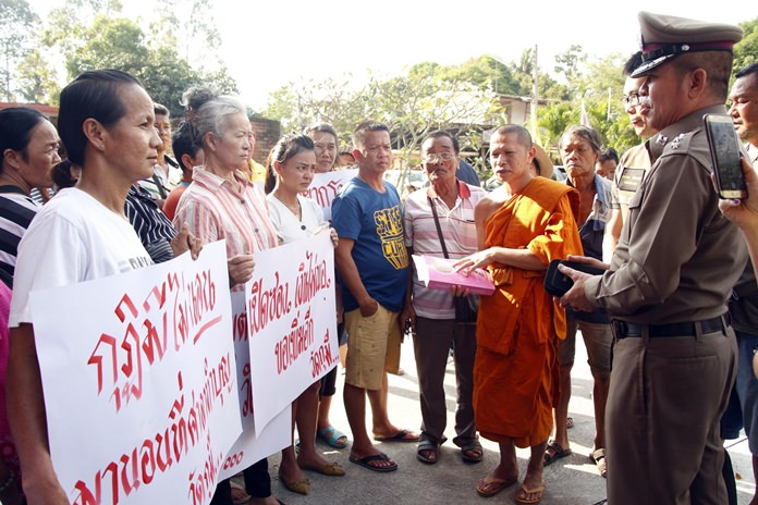 Huay Yai's Ecclesiastical Chief Wikomsatsanakit and Police Chief Pol. Lt. Col. Anan Purahong receive the protestors' written petition arguing temple Abbot Wichaiworawad Tamwaro has been discriminating against poor neighbors.