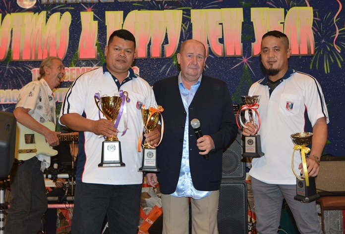 Paul Conwell introduces the PSC Darts team champions Kenneth Magdalene and Rolly Gabiani, proudly holding their champions' trophies won at the Chiang Mai, Bangkok and Lampang tournaments.