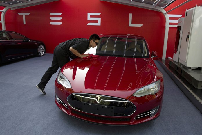 In this April 22, 2014, file photo, a worker cleans a Tesla Model S sedan before an event to deliver the first set of cars to customers in Beijing, China. (AP Photo/Ng Han Guan)