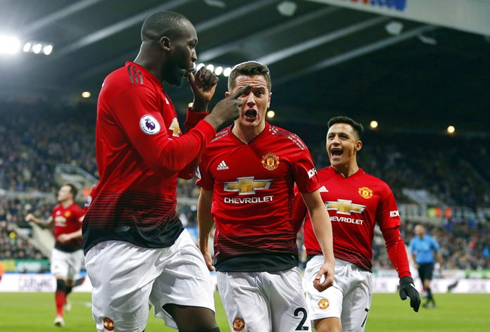 Manchester United's Romelu Lukaku, left, celebrates with teammates after scoring his side's first goal of the game against Newcastle United at St James' Park in Newcastle, Wednesday, Jan. 2. (Owen Humphreys/PA via AP)