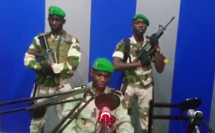 In this image from TV, a soldier who identified himself as Lt. Obiang Ondo Kelly, commander of the Republican Guard, reads a statement on state television broadcast from Libreville, Gabon, saying the military has seized control of the government, Monday Jan. 7. (Gabon State TV via AP)
