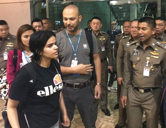 Saudi woman Rahaf Mohammed Alqunun, foreground walks by Chief of Immigration Police Maj. Gen. Surachate Hakparn, right, before leaving the Suvarnabhumi Airport in Bangkok Monday, Jan. 7. (Immigration police via AP)