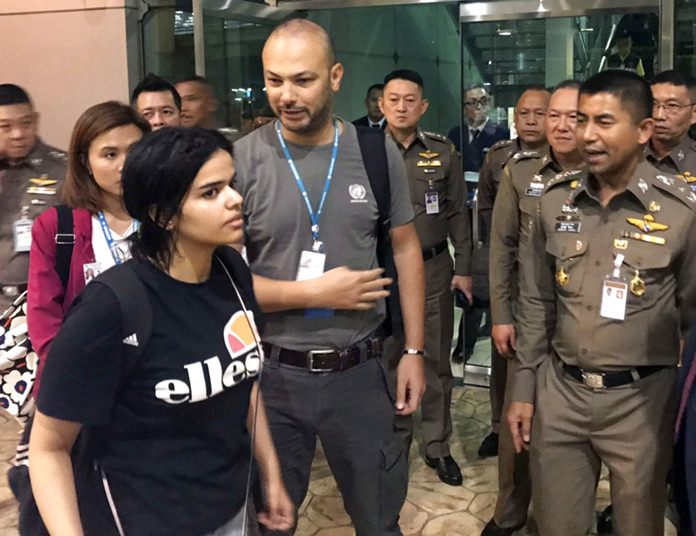 In this Jan. 7, 2019, file photo, Saudi woman Rahaf Mohammed Alqunun, foreground, walks by Chief of Immigration Police Maj. Gen. Surachate Hakparn, right, before leaving Suvarnabhumi Airport in Bangkok. (Immigration police via AP)