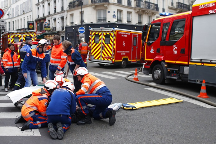 Firefighters tend to a wounded person near the site of a gas leak explosion in Paris, France, Saturday, Jan. 12. (AP Photo/Thibault Camus)