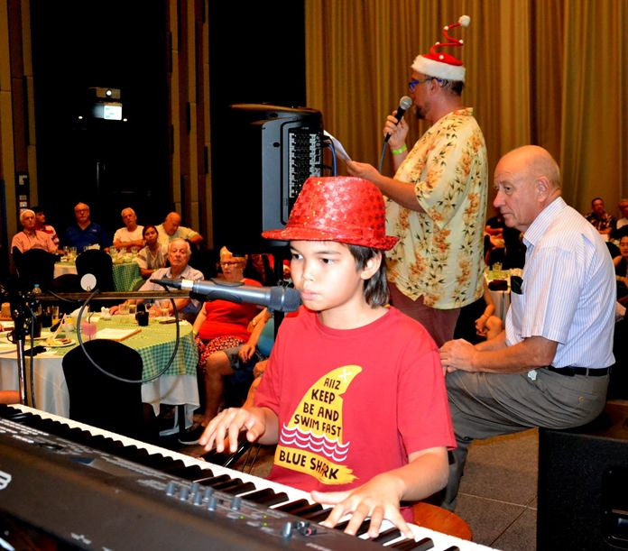 Ben Rudolf stands ready at the keyboard as Marcus Tristan (with microphone) prepares everyone to join in with the singing of Christmas Carols.