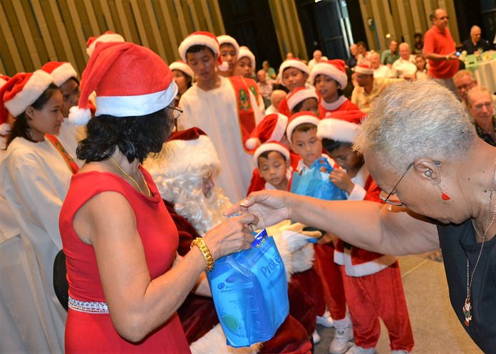 Father Christmas greeted the children from the choir and with the aid of his helpers, each child was presented with a bag full of goodies.