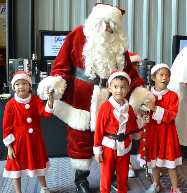 Several members of the younger Pattaya Orphanage Choir happily welcome Father Christmas to the PCEC festivities.
