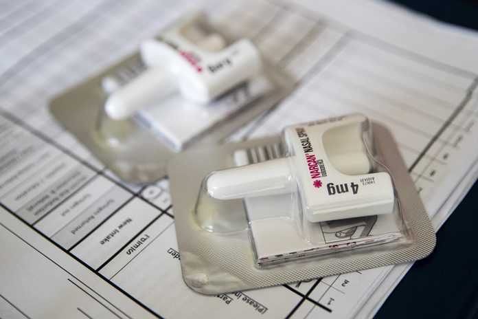 In this Tuesday, July 3, 2018 file photo, a Narcan nasal device which delivers naloxone lies on a counter as a health educator gives instructions on how to administer it in the Brooklyn borough of New York. On Wednesday, Dec. 19, 2018, the U.S. government told doctors to consider prescribing the overdose antidote naloxone to many more patients who take opioid painkillers. (AP Photo/Mary Altaffer)
