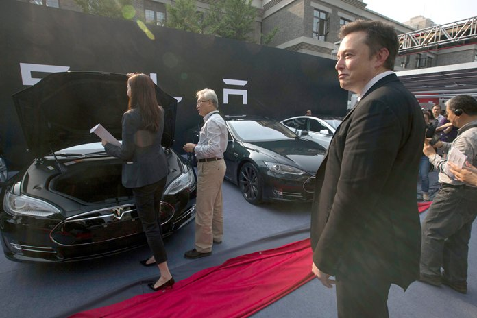 In this April 22, 2014, file photo. Tesla Motors CEO Elon Musk (right) looks on as a set of Tesla Model S sedans are delivered to customers at an event in Beijing, China. (AP Photo/Ng Han Guan)