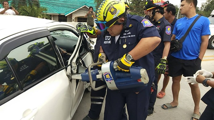 Rescue personnel use jaws-of-life to extricate an unidentified accident victim in Nongprue.