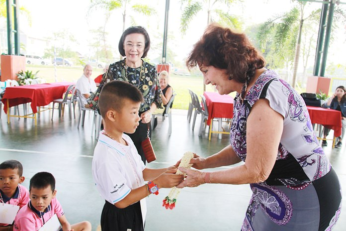 Pattaya Blatt Executive Editor Elfi Seitz receives a garland of thanks from a young gentleman from the Human Help Network Foundation Thailand (HHNFT).