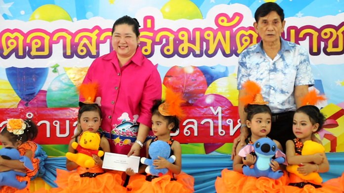 Former Culture Minister Sukumol Kunplome (left) helps hand out toys in Nong Plalai.