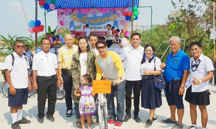 Chonburi Provincial Councilor Sakol Phonlookin and friends give away bicycles to children in Naklua's Hua Tung Community.