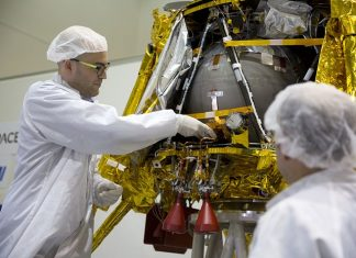 "SpaceIL co-founder Yonatan Winetraub, left, inserts a time capsule into the SpaceIL lunar module, an unmanned spacecraft, that is on display in a special ""clean room"" where the space craft is being developed, during a press tour of their facility near Tel Aviv, Israel, Monday, Dec. 17, 2018. SpaceIL and the state-owned Israel Aerospace Industries plan to launch their unmanned spacecraft to the moon early in 2019. (AP Photo/Ariel Schalit)"