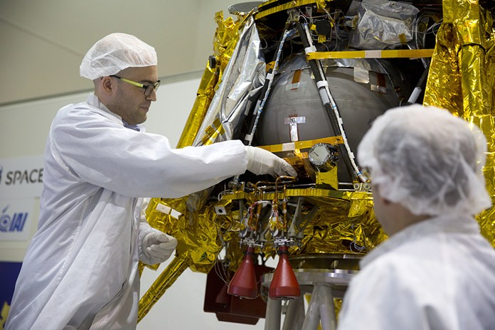 """SpaceIL co-founder Yonatan Winetraub, left, inserts a time capsule into the SpaceIL lunar module, an unmanned spacecraft, that is on display in a special """"clean room"""" where the space craft is being developed, during a press tour of their facility near Tel Aviv, Israel, Monday, Dec. 17, 2018. SpaceIL and the state-owned Israel Aerospace Industries plan to launch their unmanned spacecraft to the moon early in 2019. (AP Photo/Ariel Schalit)"""
