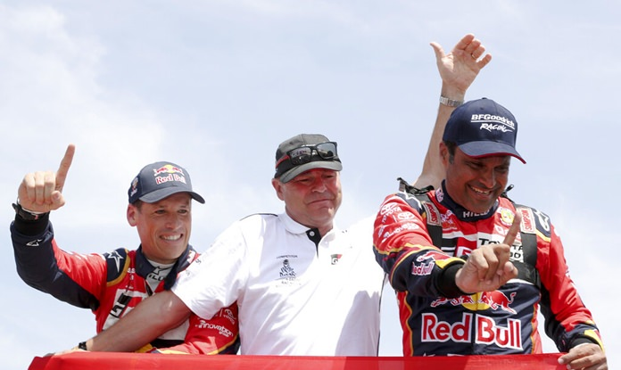 Driver Nasser Al-Attiyah, of Qatar (right) and co-driver Matthieu Baumel, of France (left) celebrate with Toyota team manager Glyn Hall after winning the Dakar Rally at the arrival of the last stage in Pisco, Peru, Thursday, Jan. 17. (AP Photo/Ricardo Mazalan)