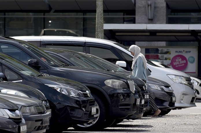 A woman walks toward her car in a parking lot in Putrajaya, Malaysia, Wednesday, Jan. 16. (AP Photo/Yam G-Jun)